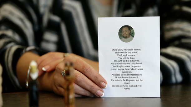 In this photo taken Wednesday, March 6, 2019 in Raleigh, N.C. Heather Allen holds a photo of her father, Lee Wayne Hunt, from his memorial. Even though Lee Wayne Hunt died as a prisoner found guilty of a double murder, his family says he never gave up hope of proving his innocence. (AP Photo/Gerry Broome)