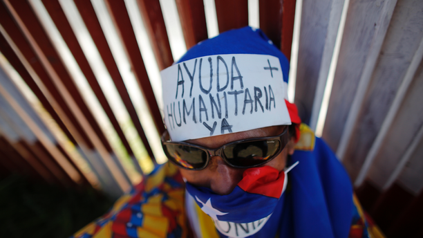 "FILE - In this Feb. 23, 2019 file photo, an opposition supporter wears a message on his forehead that reads in Spanish: ""Humanitarian aid now,"" during a demonstration urging soldiers to allow the entry of U.S. humanitarian aid, in Caracas, Venezuela. Human Rights Watch and public health researchers from Johns Hopkins are urging the United Nations, who are meeting Wednesday, April 10, 2019, to declare the situation in Venezuela ""a complex humanitarian emergency that poses a serious risk to the region."" (AP Photo/Ariana Cubillos, File)"