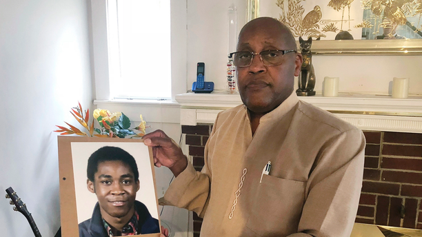 FILE - In this Sept. 5, 2018 file photo, Dia Khafra, father of Askia Khafra, holds a photo of his son in his Silver Springs, Md., home. Jurors are set to hear closing arguments Tuesday, April 23, 2019, in the trial of Daniel Beckwitt, a 27-year-old millionaire. Beckwitt is charged with second-degree murder and involuntary manslaughter in the September 2017 death of 21-year-old Askia Khafra. A fire erupted and killed Khafra, who was helping Beckwitt dig tunnels for an underground nuclear bunker. (AP Photo/Michael Kunzelman, File)
