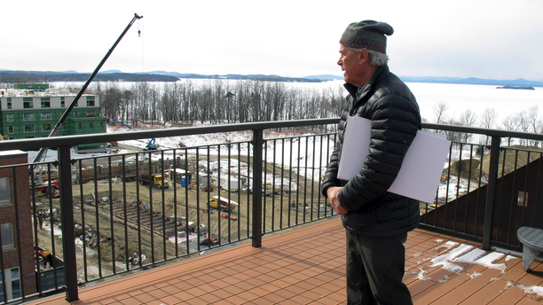 In this March 7, 2019 photo, developer Eric Farrell looks at construction on the property that once housed Burlington College, and before that was an orphanage run by the Roman Catholic Diocese, on the shore of ice-covered Lake Champlain, background, in Burlington, Vt. The property is being redeveloped and city officials say it will be a boost to the entire community. (AP Photo/Wilson Ring)