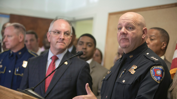 """Louisiana State Fire Marshal H. """"Butch"""" Browning speaks as Louisiana Gov. John Bel Edwards looks on during a press conference on the arrest of a suspect Holden Matthews for the arson of three churches in Opelousas, La., Thursday, April 11, 2019. (AP Photo/Lee Celano)"""