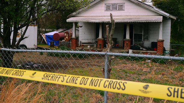 In this Friday, April 5, 2019, photo, police tape marks the area where the Spartanburg County Sheriff's Office and Spartanburg County Coroner's were working after two bodies were found buried on the property on Williams Street in Spartanburg, S.C. Two men have been charged with murder in connection with the discovery. (Tim Kimzey/Spartanburg Herald-Journal via AP)