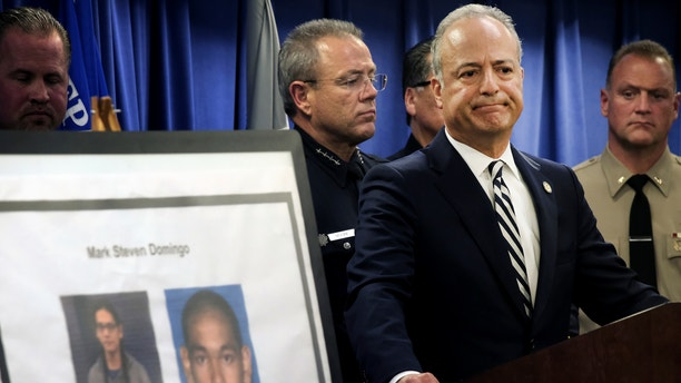 United States Attorney Nick Hanna stands next to photos of Mark Steven Domingo, during a news conference in Los Angeles on Monday, April 29, 2019. A terror plot by Domingo, an Army veteran who converted to Islam and planned to bomb a white supremacist rally in Southern California as retribution for the New Zealand mosque attacks was thwarted, federal prosecutors said Monday. (AP Photo/Richard Vogel)