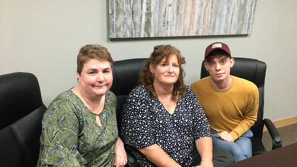 In this Sunday, April 14, 2019, photo, RJR Maintenance and Management office manager Deanna Finnie, left, co-owner Jackie Fakler, center, and marketing executive Ben Pace pose for a photograph at the business in Mandan, N.D., where four people were brutally slain on April 1. Chiropractor Chad Isaak, who lived on property managed by the company, is charged with felony murder in the deaths of co-owner Robert Fakler, Jackie's husband, and three workers. (AP Photo/Blake Nicholson)