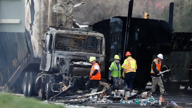 "Workers clear debris from the eastbound lanes of Interstate 70 on Friday, April 26, 2019, in Lakewood, Colo., a deadly pileup involving semi-truck hauling lumber on Thursday. Lakewood police spokesman John Romero described it as a chain reaction of crashes and explosions from ruptured gas tanks. ""It was crash, crash, crash and explosion, explosion, explosion,"" he said. (AP Photo/David Zalubowski)"