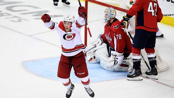 Carolina Hurricanes left wing Brock McGinn, left, celebrates his game-winning goal during double overtime of Game 7 of an NHL hockey first-round playoff series against Washington Capitals goaltender Braden Holtby (70) and right wing Tom Wilson (43), Wednesday, April 24, 2019, in Washington. The Hurricanes won 4-3 in double overtime. (Associated Press)