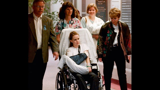 Kacey Ruegsegger, 17, is wheeled from a Denver hospital by Patty Anderson, center, after being released in May 1999. Walking beside her are her parents Greg, left, and Darcy, right. Ruegsegger Johnson survived a shotgun blast during the shootings at Colorado's Columbine High School that left 12 students, one teacher, and both gunmen dead.