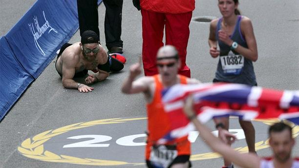 Micah Herndon, of Tallmadge, Ohio, crawls to the finish line in the 123rd Boston Marathon on Monday, April 15, 2019, in Boston. (AP Photo/Charles Krupa)