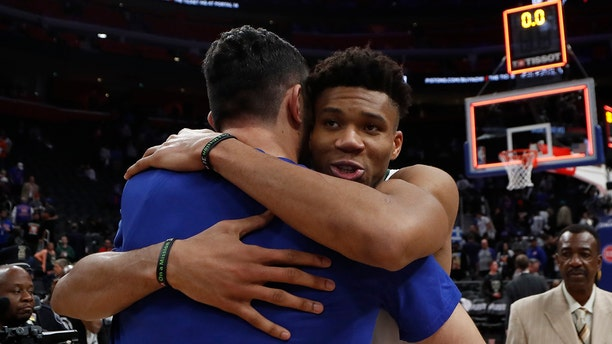 Milwaukee Bucks forward Giannis Antetokounmpo, front right, hugs Detroit Pistons center Zaza Pachulia after Game 4 of a first-round NBA basketball playoff series, Monday, April 22, 2019, in Detroit. (AP Photo/Carlos Osorio)