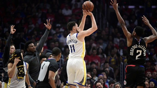 Golden State Warriors guard Klay Thompson, left, shoots as Los Angeles Clippers guard Shai Gilgeous-Alexander defends during the first half in Game 4 of a first-round NBA basketball playoff series Sunday, April 21, 2019, in Los Angeles. (AP Photo/Mark J. Terrill)