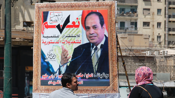 "People walk past a banner supporting proposed amendments to the Egyptian constitution with a poster of Egyptian President Abdel-Fattah el-Sissi in Cairo, Egypt, Tuesday, April 16, 2019. Egypt's parliament was holding its last debate Tuesday on proposed amendments to the constitution that could see President Abdel-Fattah el-Sissi remain in power until 2030. Arabic reads, ""do the right thing, yes to the developments, stability and amendments to the the constitution"".(AP Photo/Amr Nabil)"