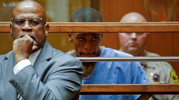 Eric Holder, the suspect in the killing of rapper Nipsey Hussle, is seen in Los Angeles County Superior Court with his attorney Christopher Darden, left, on Thursday. (Associated Press)