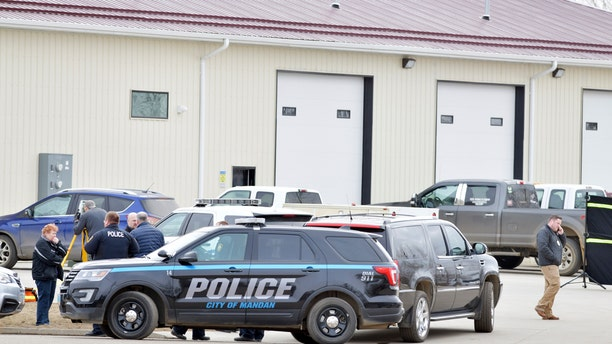 Law enforcement officers stand outside RJR Maintenance and Management in Mandan, North Dakota on Monday, where four people were found dead.