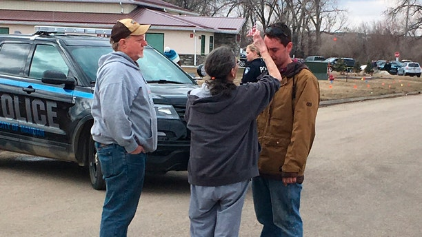 Gina Kessel, center, comforts her son Mitchell outside of RJR Maintenance and Management, a property management company, Monday, April 1, 2019, Mandan, N.D.