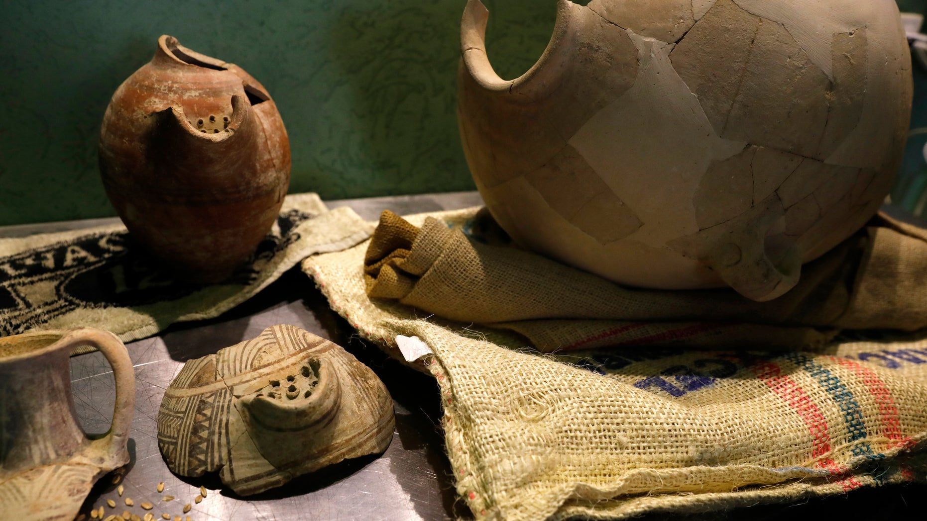 Ancient jars are on display during a press conference in Jerusalem, Wednesday, May 22, 2019. Israeli researchers celebrated Wednesday a long-brewing project of making beer and mead using yeasts extracted from ancient clay vessels -- some over 5,000 years old. (AP Photo/Sebastian Scheiner)