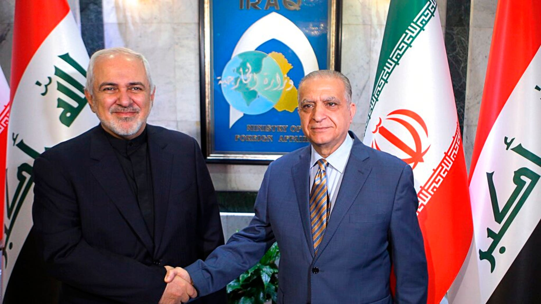 Iraqi Foreign Minister Mohamed Alhakim, right, shakes hands with his visiting Iranian counterpart Mohammad Javad Zarif at the Ministry of Foreign Affairs Building in Baghdad, Iraq.