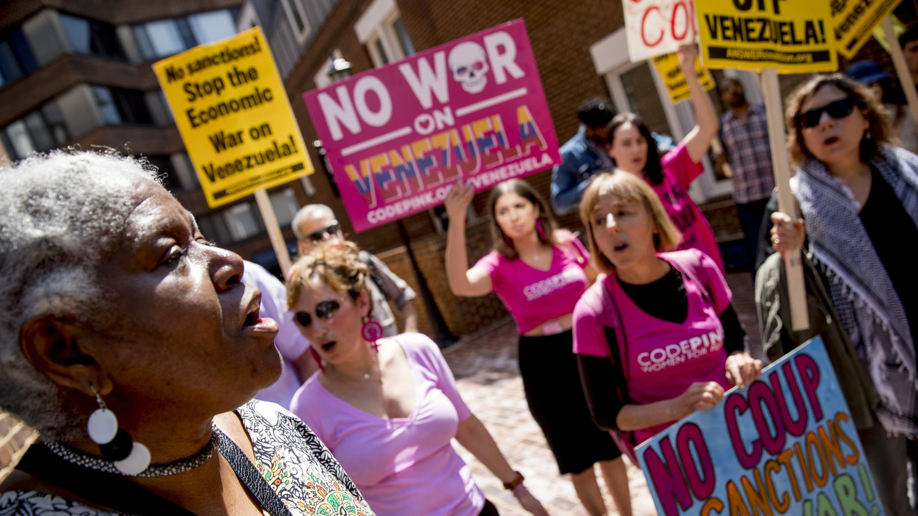 U.S. activist Medea Benjamin, co-founder of the antiwar group Code Pink, second from right, and others, sing together outside the Venezuelan Embassy in Washington on Thursday. Supporters of interim government opposition leader Juan Guaido have blocked the entrances to the embassy, cutting off supplies to backers of embattled leader Nicolas Maduro supporters occupying the building. (AP Photo/Andrew Harnik)