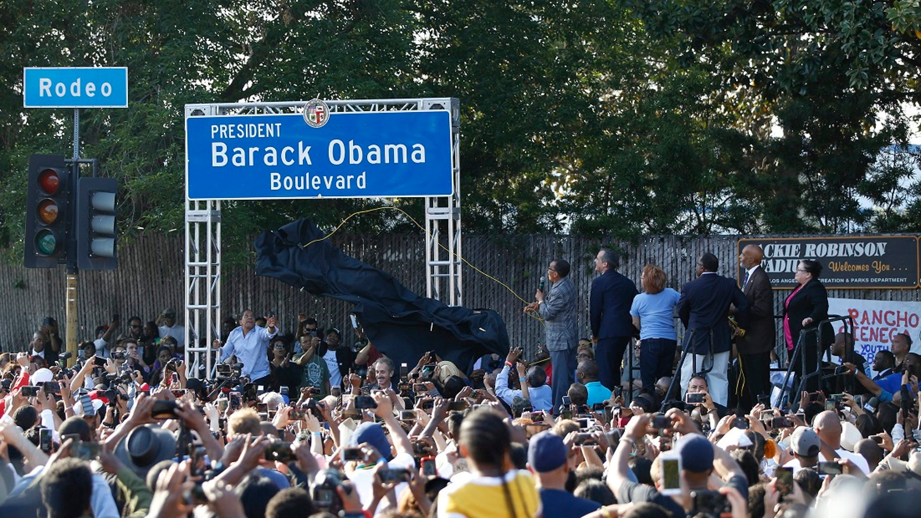 """City officials, at podium on right, unveil the """"President Barack Obama Boulevard"""" sign in Los Angeles on Saturday. (Associated Press)"""
