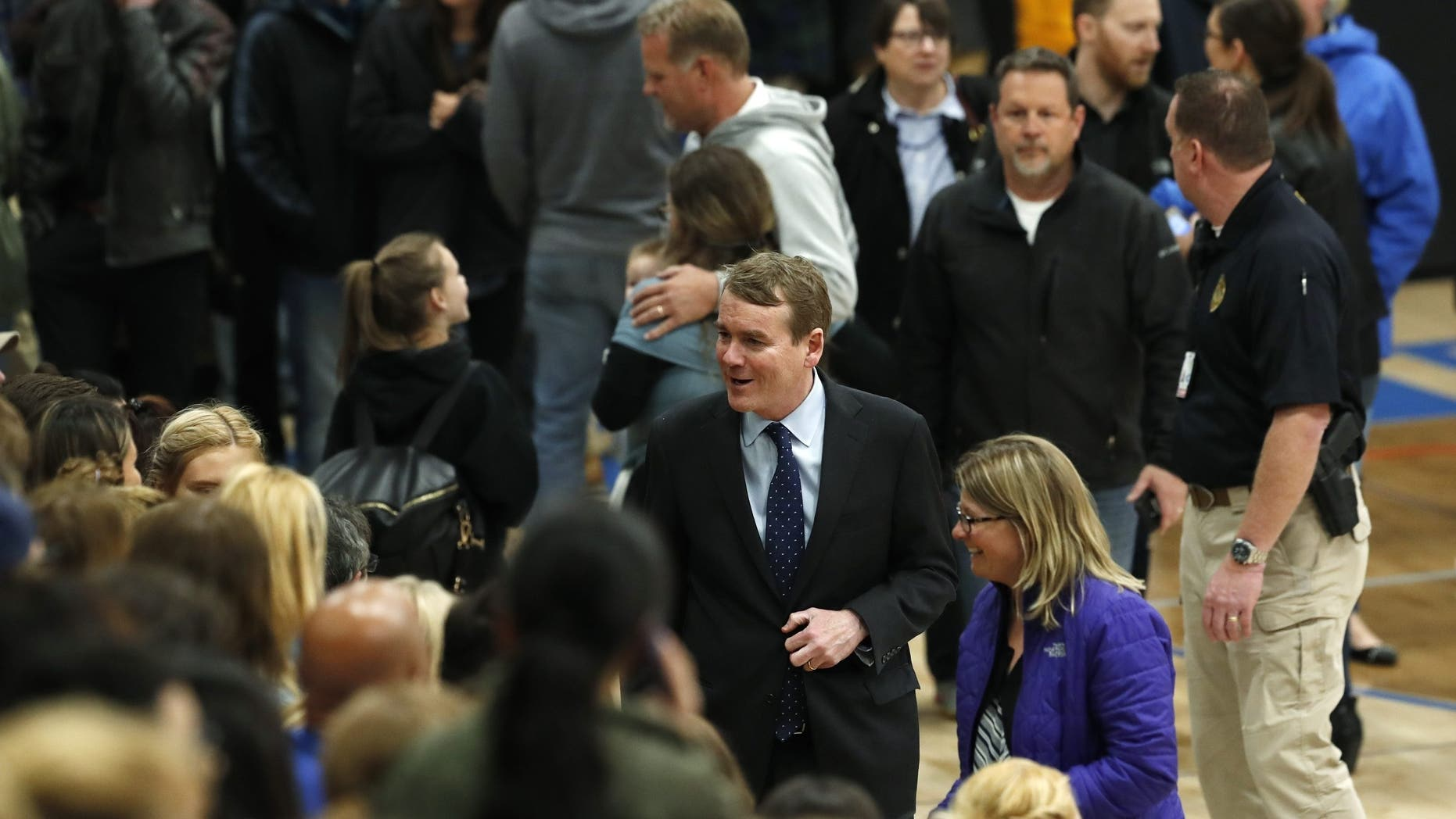 U.S. Sen. Michael Bennet, D-Colo., center, greets attendees during a community vigil to honor the victims and survivors of yesterday's fatal shooting at the STEM School Highlands Ranch, on Wednesday, May 8, 2019, in Highlands Ranch, Colo. (AP Photo/David Zalubowski)