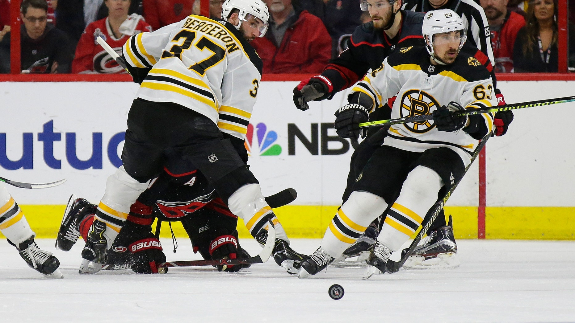 Boston Bruins' Patrice Bergeron (37) and Brad Marchand (63) skate for the puck with Carolina Hurricanes' Brett Pesce (22) and Jordan Staal during the second period in Game 3 of the NHL hockey Stanley Cup Eastern Conference final series in Raleigh, N.C., Tuesday, May 14, 2019. (Associated Press)