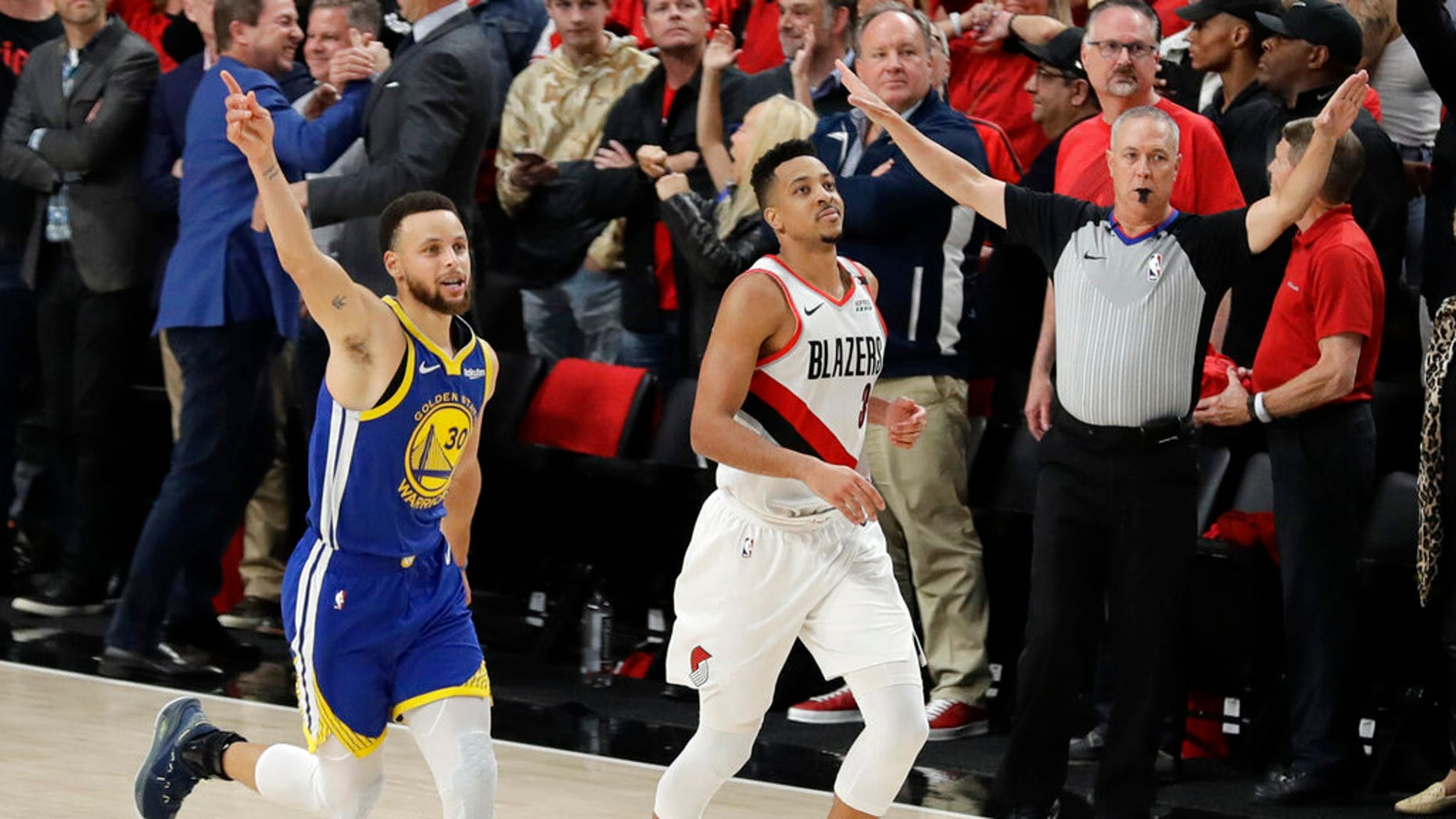 Golden State Warriors guard Stephen Curry, left, celebrates as he runs next to Portland Trail Blazers guard CJ McCollum, center, at the end of Game 4 of the NBA basketball playoffs Western Conference finals.