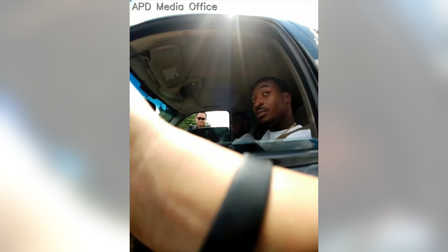 In this screenshot taken from Sept. 1, 2018, police body camera video provided by the Arlington Police Department, an officer, foreground, talks to O'Shae Terry after stopping him for a vehicle registration violation, in Arlington, Texas, as a second officer, background left, looks in from the passenger side window. Bau Tran, a Texas police officer has been fired after he was charged with criminally negligent homicide in the fatal shooting of a black man during a traffic stop last year. In a statement Friday, May 17, 2019 Arlington police announced Officer Bau Tran was fired after an internal investigation found policy violations that led to the Sept. 1 shooting of 24-year-old O'Shae Terry. (Arlington Police Department via AP, File)