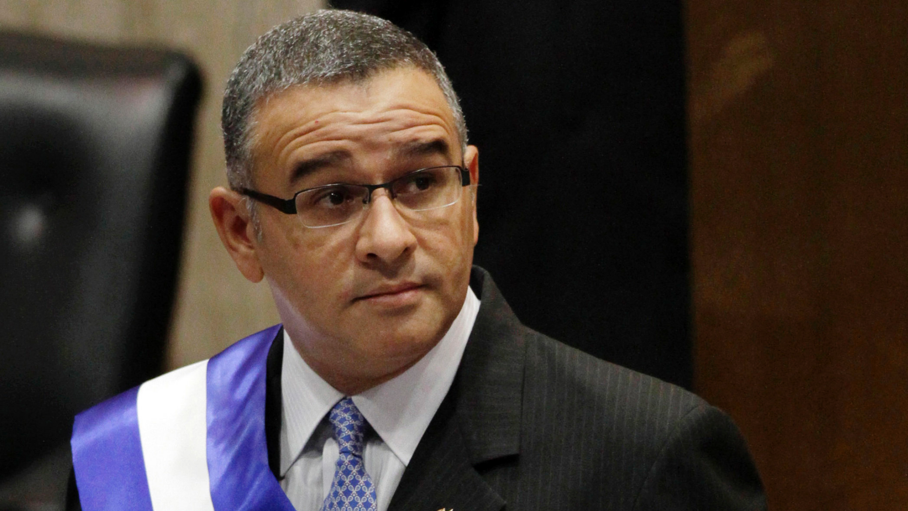 FILE - In this June 1, 2012 file photo, El Salvador's President Mauricio Funes stands in the National Assembly before speaking to commemorate the anniversary of his third year in office in San Salvador, El Salvador. Funes, who is a fugitive of El Salvador's courts and lives under political asylum in Nicaragua, said Monday, May 13, 2019, that he is working as an adviser to the government of Nicaraguan President Daniel Ortega.  (AP Photo/Luis Romero, File)