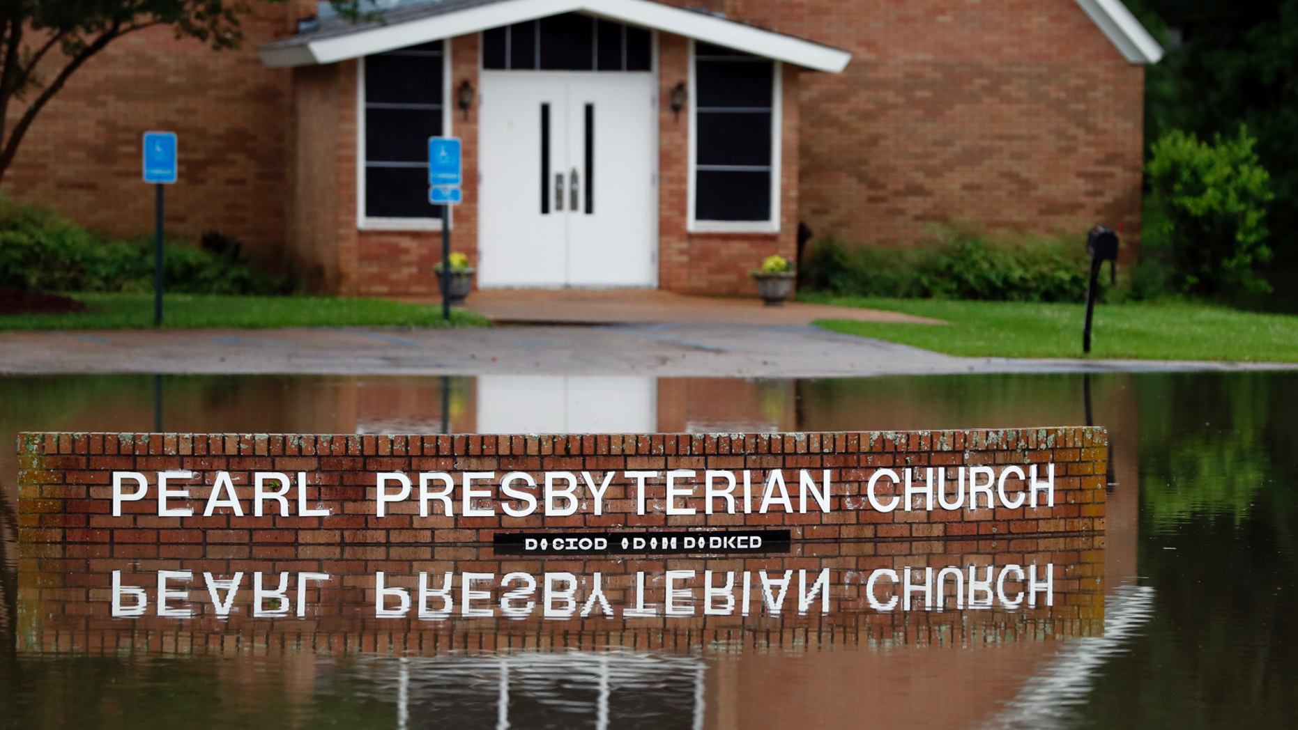 The Pearl Presbyterian Church's sign is reflected in floodwaters in Pearl, Miss., on Thursday, May 9, 2019. There is no pond on the property and the flash flooding filled up the parking lot as it surrounded the church. Strong winds, tornado warnings and substantial rains added to the flash flooding throughout Mississippi including this area of downtown Jackson, Miss., Thursday, May 9, 2019. (AP Photo/Rogelio V. Solis)
