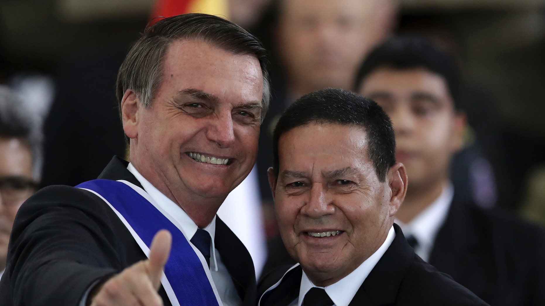 Brazil's President Jair Bolsonaro flashes a thumbs up after bestowing the insignia of the Order of Rio Branco to Vice President Hamilton Mourao, right, during a ceremony to commemorate Diplomat Day, at the Itamarty Palace in Brasilia, Brazil, Tuesday, May 3, 2019. (AP Photo/Eraldo Peres)