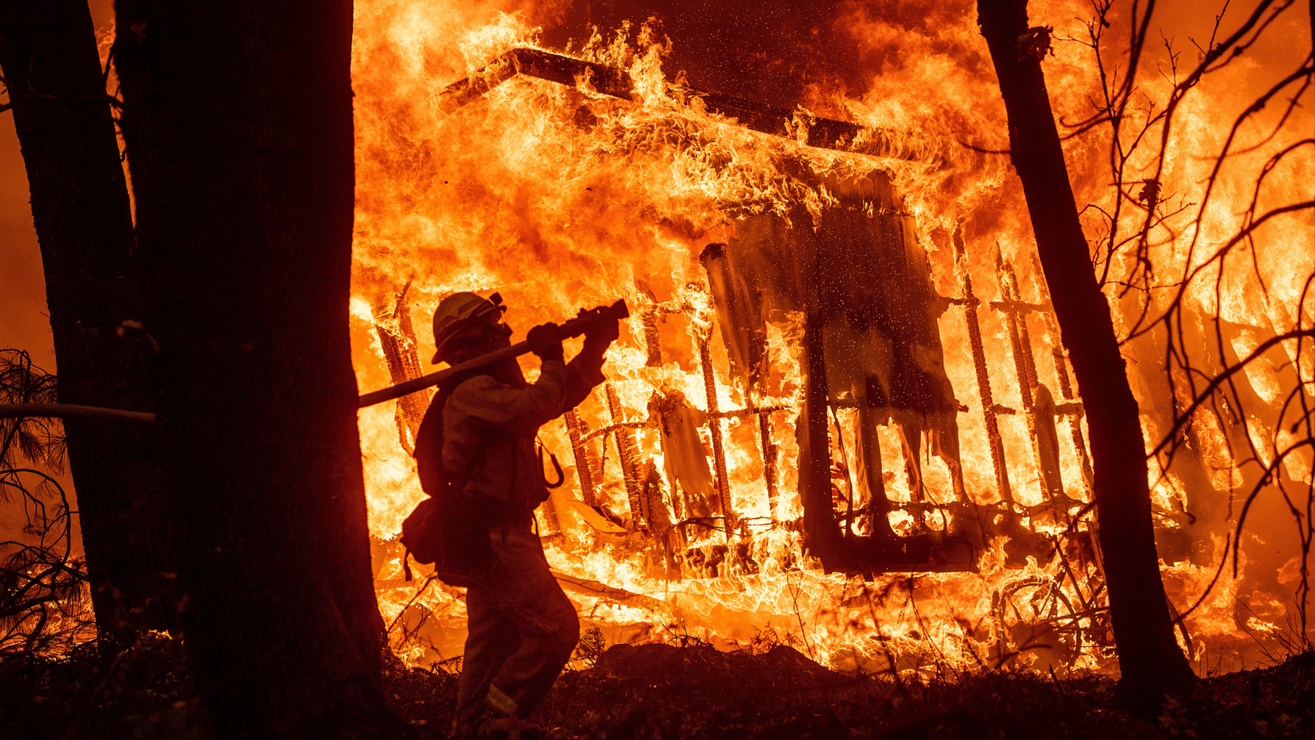 FILE - In this Nov. 9, 2018 file photo, firefighter Jose Corona sprays water as flames from the Camp Fire consume a home in Magalia, Calif. Federal officials say an effort to develop a better fire shelter following the deaths of 19 wildland firefighters in Arizona six years ago has failed. Officials at the National Interagency Fire Center in Boise in a decision on Wednesday, May 15, 2019 say the current fire shelter developed in 2002 will remain in use, saying the current shelter combines the most practical level of protection balanced against weight, bulk and durability. (AP Photo/Noah Berger, File)