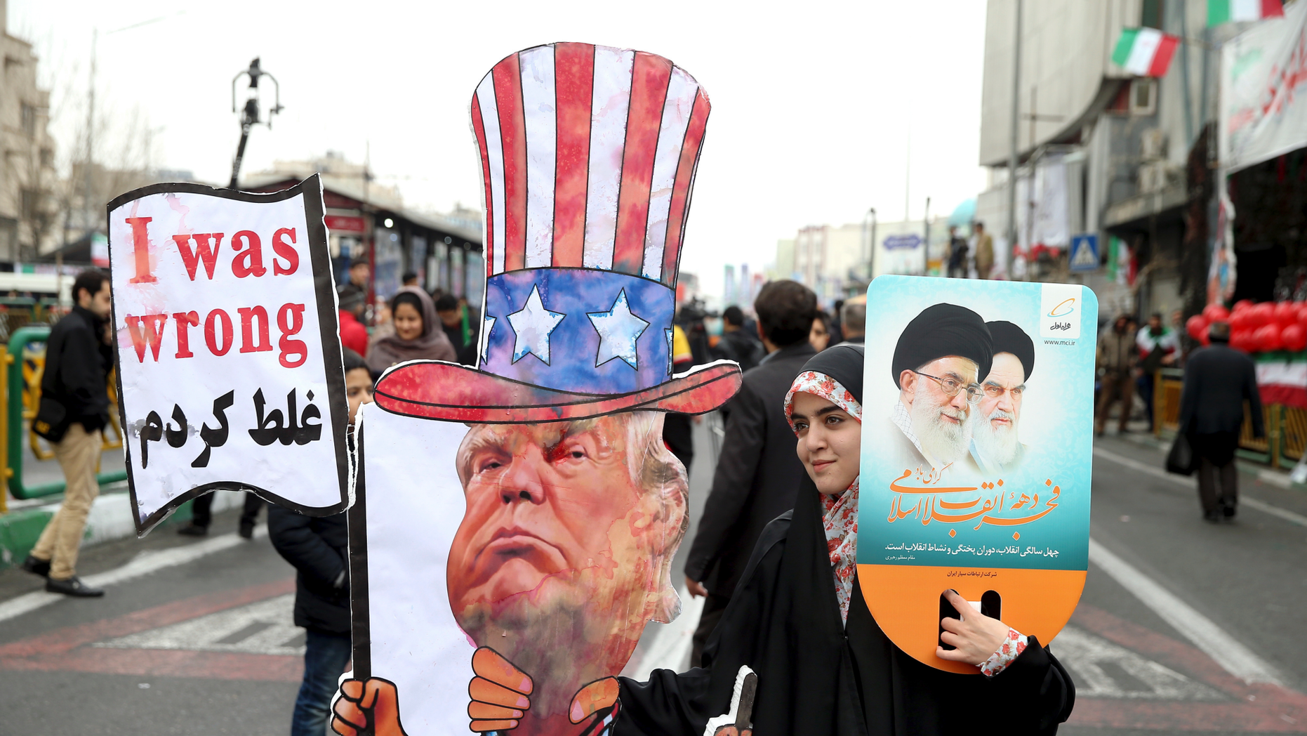 FILE - In a Feb. 11, 2019 file photo, an Iranian woman holds an effigy of US president Donald Trump, during a rally marking the 40th anniversary of the 1979 Islamic Revolution, in Tehran, Iran. Iranian President Hassan Rouhani is reportedly set to announce Wednesday, May 8, 2019, ways the Islamic Republic will react to continued U.S. pressure after President Donald Trump pulled America from Tehran's nuclear deal with world powers. (AP Photo/Ebrahim Noroozi, File)
