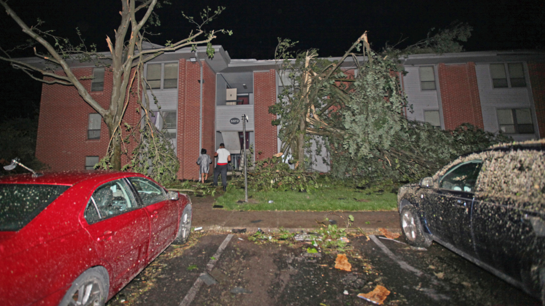 """Residents walk toward their Westbrooke Village Apartment building that was heavily damaged by a tornado Tuesday morning, May 28, 2019, in Dayton, Ohio. The Ohio Department of Transportation is using snow plows to remove debris off an Ohio highway after a """"large and dangerous"""" tornado hit the area late Monday. (Doral Chenoweth III/Columbus Dispatch via AP)"""