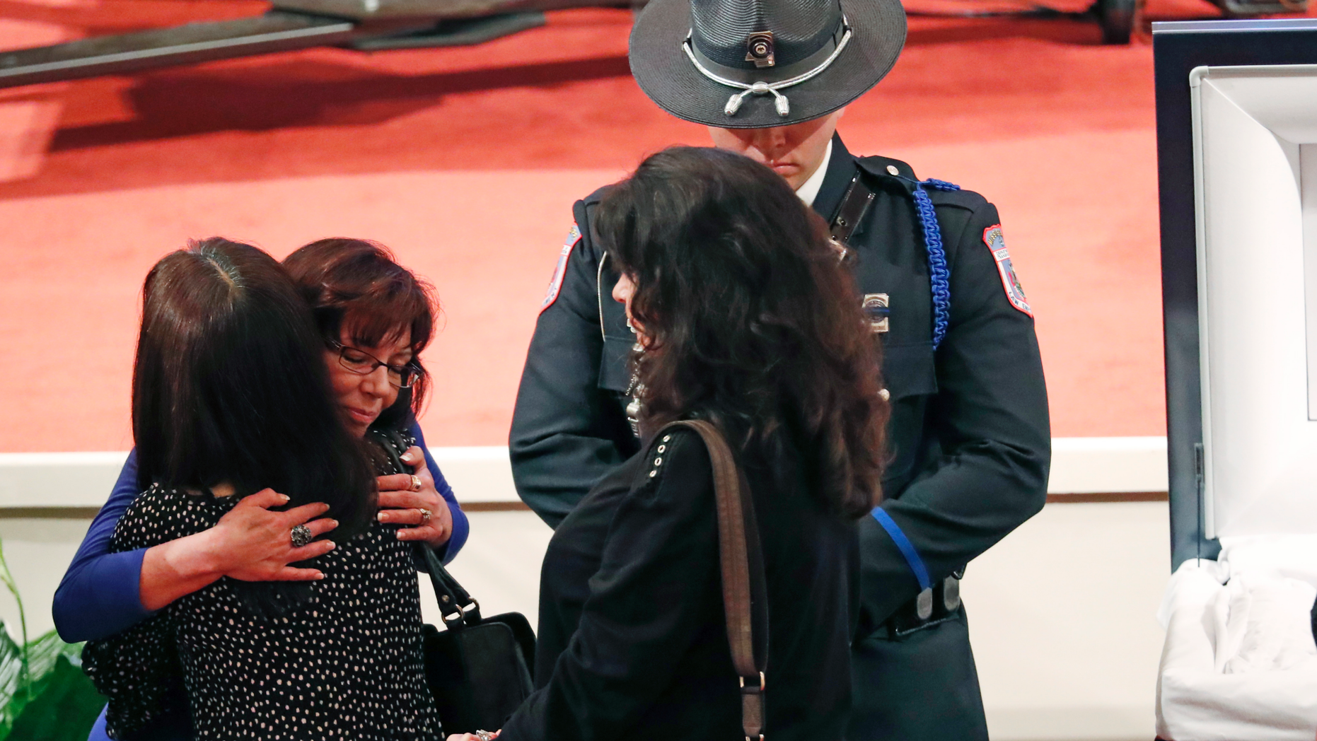 Pamela McKeithen, widow of officer Robert S. McKeithen, second from left, hugs a mourner as a member of a law enforcement agency honor guard, stands watch, as people pay their respects to McKeithen and his family in the First Baptist Church of Biloxi, Monday morning, May 13, 2019, prior to the funeral service. McKeithen was killed outside headquarters May 5. (AP Photo/Rogelio V. Solis)