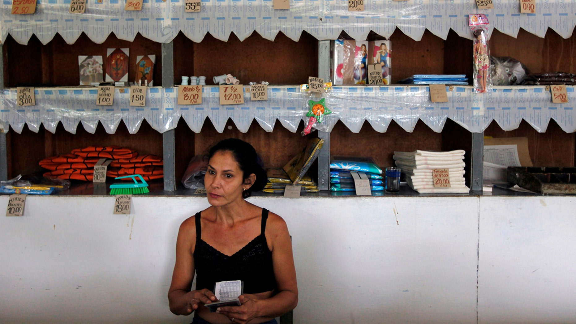 "A worker holds a rationing booklet at a government-run food store called ""Bodega"" in Sagua La Grande, Villaclara Province, central Cuba November 8, 2009. REUTERS/Desmond Boylan (CUBA SOCIETY FOOD)"