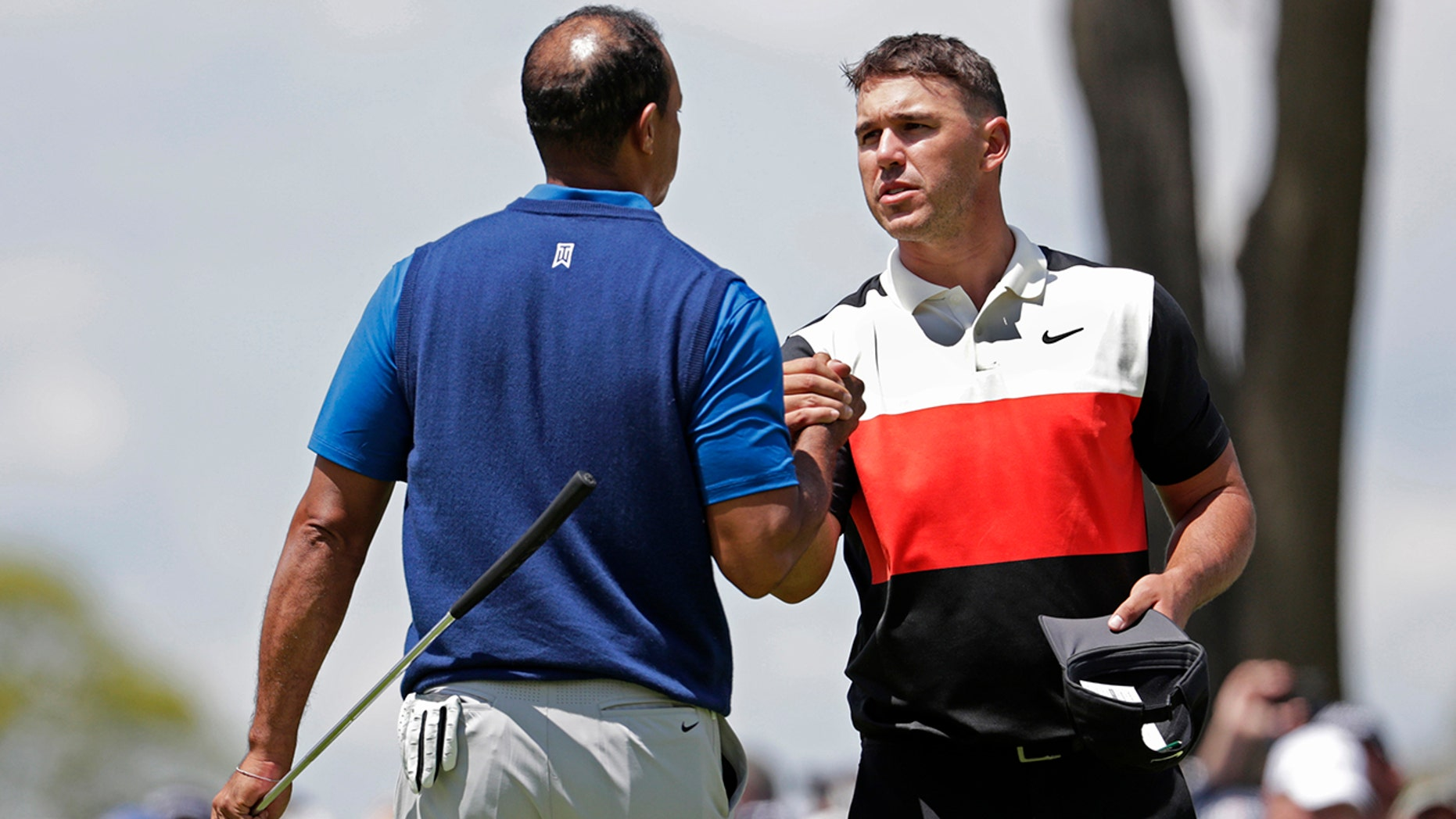 Brooks Koepka, right, shakes hands with Tiger Woods after finishing a initial turn of a PGA Championship golf tournament, Thursday, May 16, 2019, during Bethpage Black in Farmingdale, N.Y. (AP Photo/Julio Cortez)
