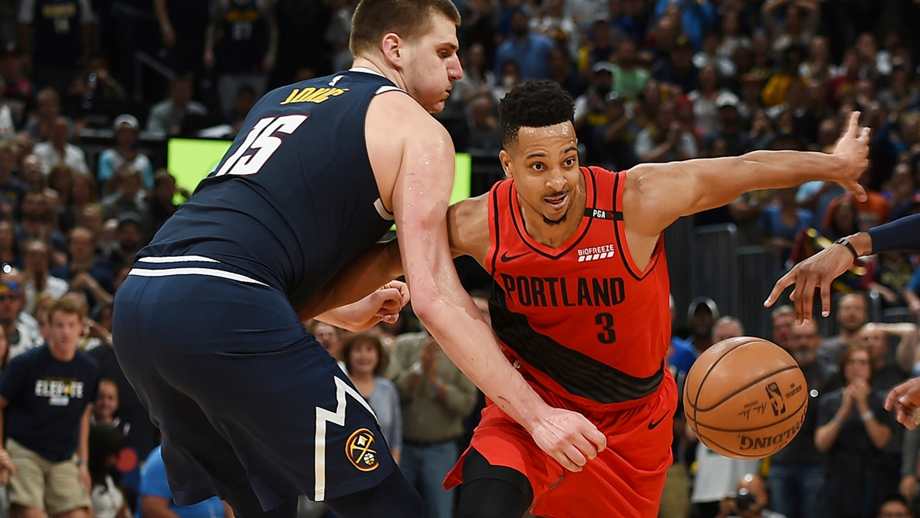 Portland Trail Blazers guard CJ McCollum, right, pursues the ball with Denver Nuggets center Nikola Jokic in the second half of Game 7 of an NBA basketball second-round playoff series Sunday, May 12, 2019, in Denver. (AP Photo/David Zalubowski)
