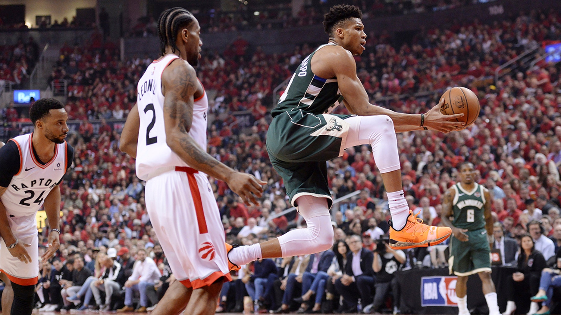 Milwaukee Bucks forward Giannis Antetokounmpo (34) drives to the net past Toronto Raptors forward Kawhi Leonard (2) during first half NBA Eastern Conference finals basketball action in Toronto on Sunday, May 19, 2019. (Nathan Denette/The Canadian Press via AP)