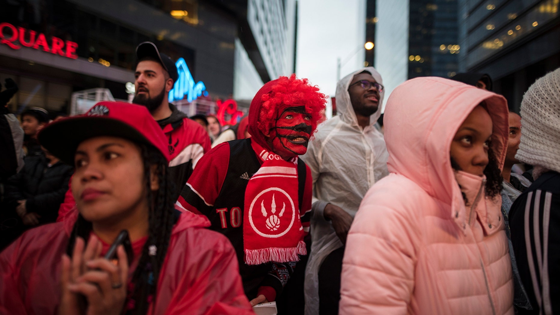 Toronto Raptors basketball fans react to game action at the Jungle Park tailgate party at Maple Leaf Square during the first half of an NBA Eastern Conference semifinal in Toronto. For Raptors games, Maple Leaf Square, aka Jurassic Park, boasts a college vibe of rowdy fans crammed into an area that covers two city blocks. (Tijana Martin/The Canadian Press via AP, File)
