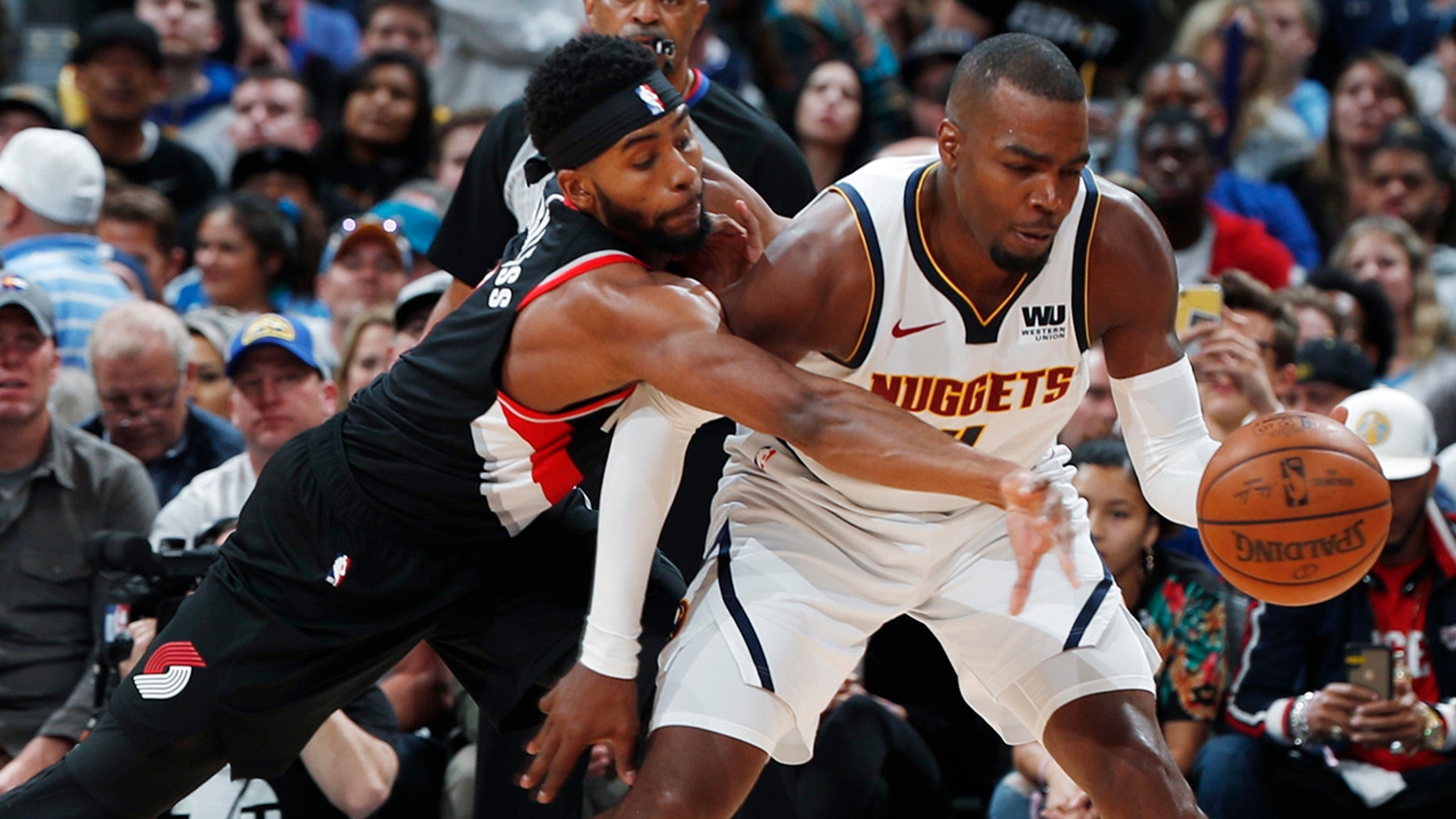 Portland Trail Blazers forward Maurice Harkless, left, tries to steal the ball from Denver Nuggets forward Paul Millsap during the second half of Game 5 of an NBA basketball second-round playoff series Tuesday, May 7, 2019, in Denver. The Nuggets won 124-98. (AP Photo/David Zalubowski)