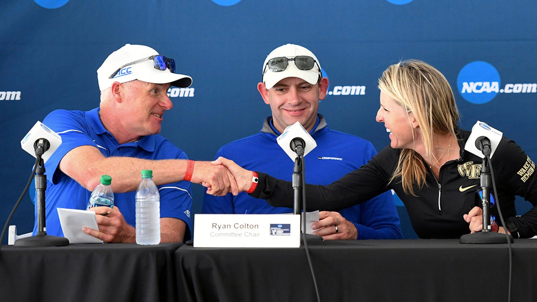 Ryan Colton, NCAA Division I Women's Golf Committee chair, center, watches as Duke women's golf coach Dan Brooks, left, shakes hands with Wake Forest women's golf coach Kim Lewellen after completing the parings for the final round of an NCAA college golf tournament, Wednesday, May 23, 2019, in Fayetteville, Ark. (AP Photo/Michael Woods)