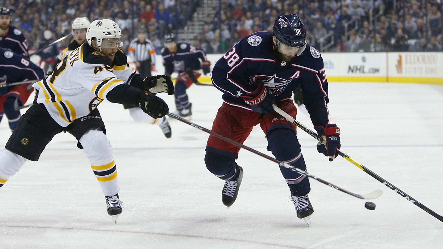 Columbus Blue Jackets' Boone Jenner, right, carries the puck up ice against Boston Bruins' Matt Grzelcyk during the second period of Game 3 of an NHL hockey second-round playoff series Tuesday, April 30, 2019, in Columbus, Ohio. (AP Photo/Jay LaPrete)
