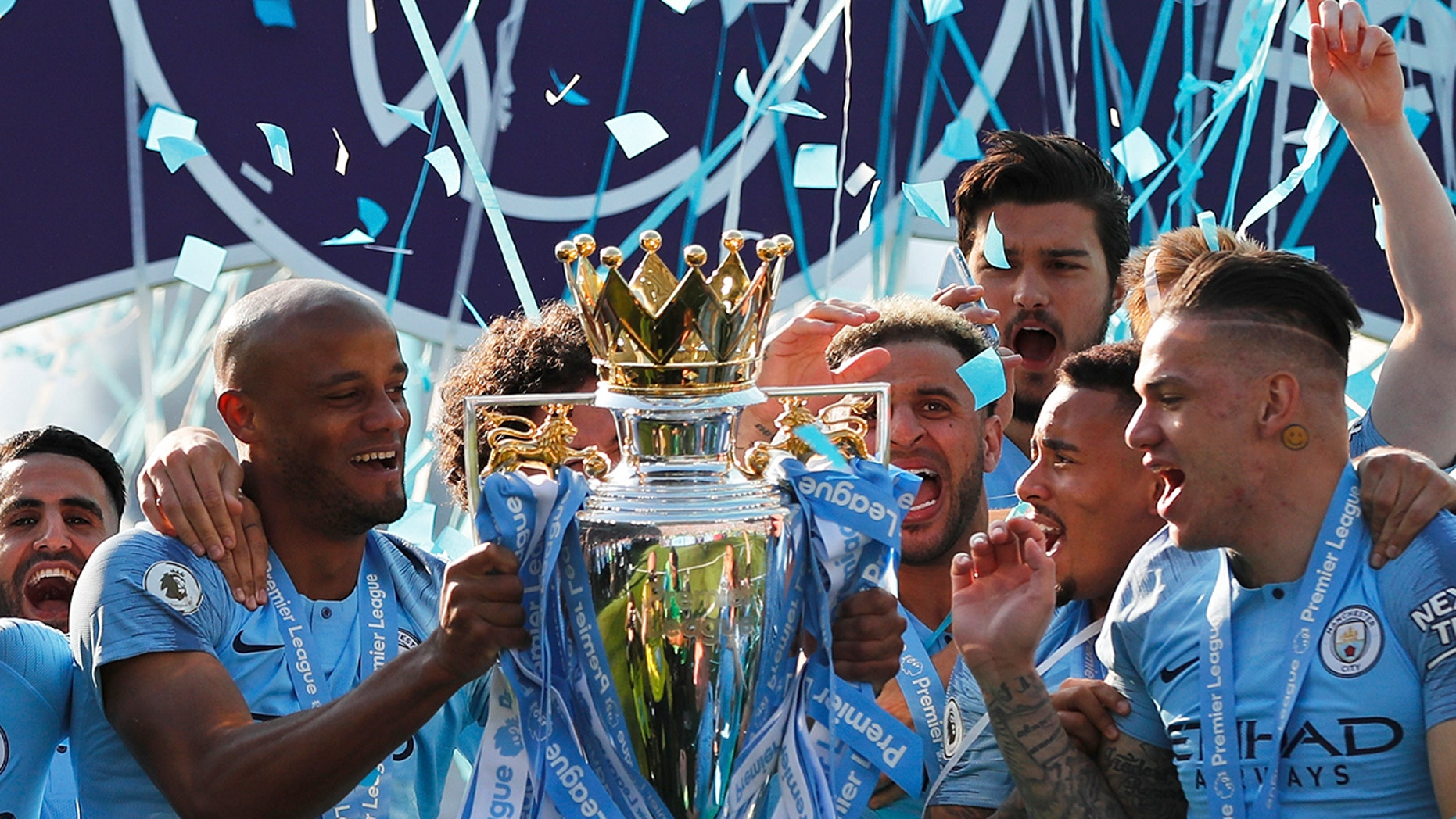 Manchester City's Vincent Kompany lifts the English Premier League trophy after the English Premier League soccer match between Brighton and Manchester City at the AMEX Stadium in Brighton, England, Sunday, May 12, 2019. Manchester City defeated Brighton 4-1 to win the championship. (AP Photo/Frank Augstein)