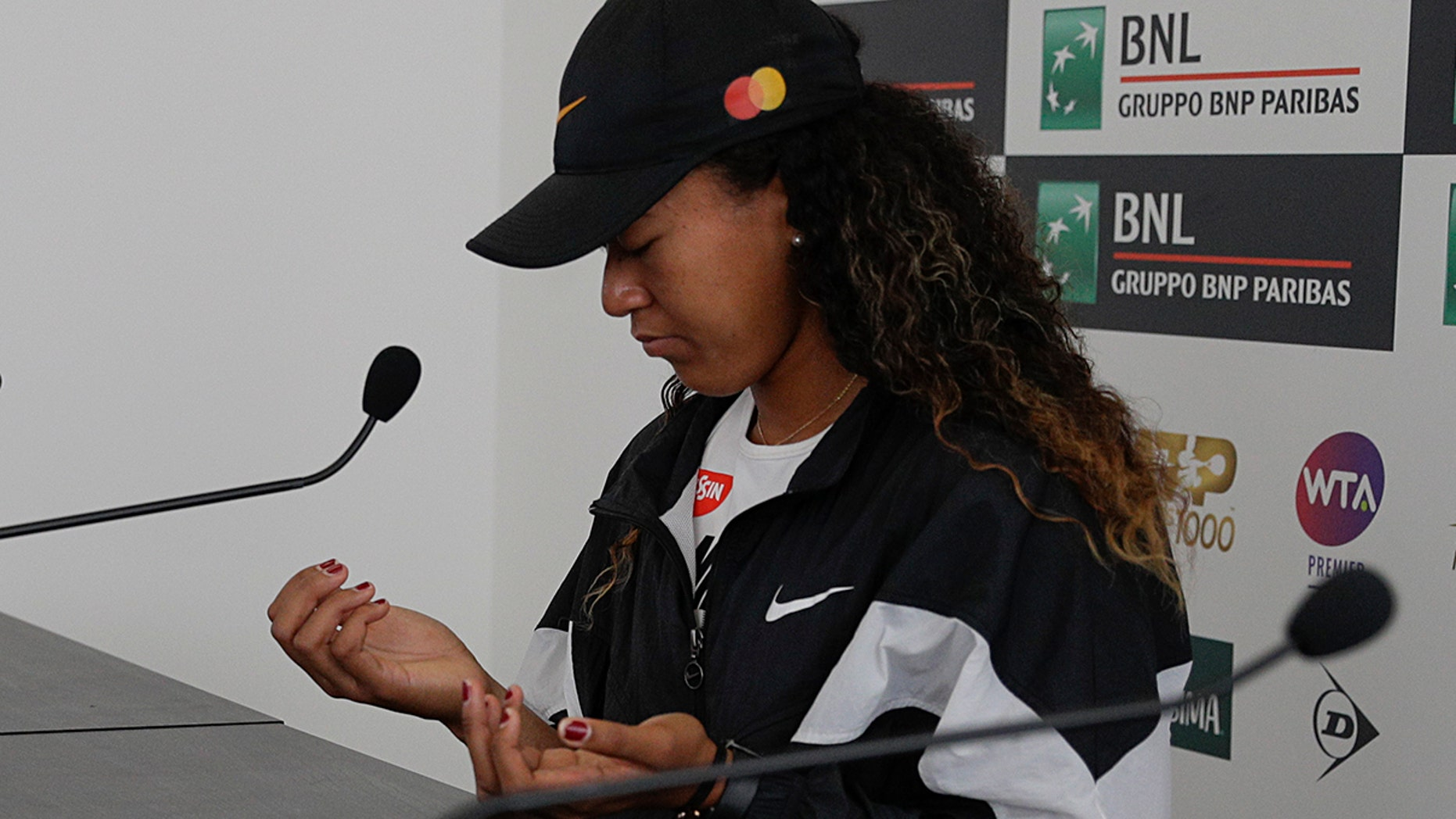 Japan's Naomi Osaka shows her hands as she meets the journalists at the Italian Open tennis tournament, in Rome, Friday, May, 17, 2019. Top-ranked Naomi Osaka withdrew from her Italian Open quarterfinal due to a right hand injury on Friday. It wasn't immediately clear how serious the injury was, or if it will affect Osaka's status for the French Open, which starts in nine days. (AP Photo/Gregorio Borgia)