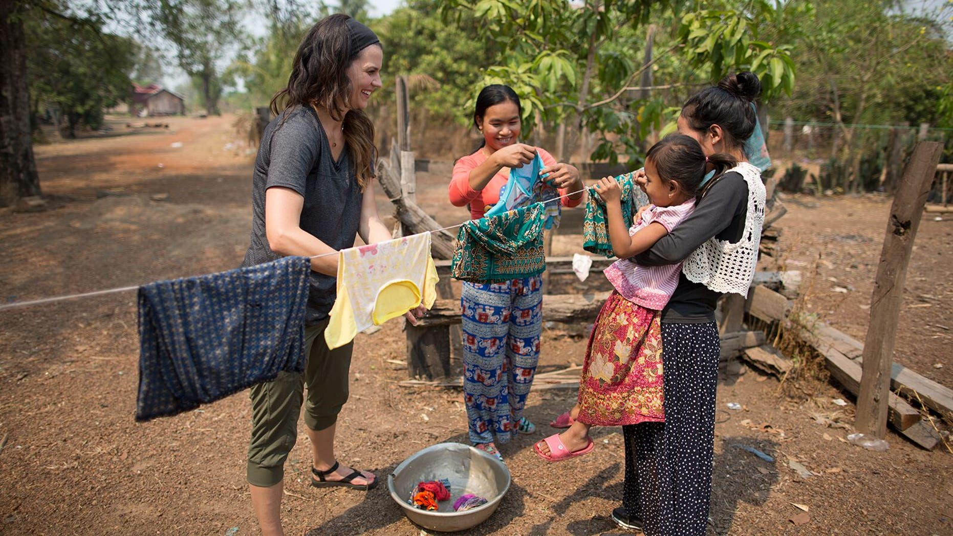 Cissie Graham Lynch works side by side with mothers in Kratie Province, Cambodia-- washing clothes and hearing about their families.