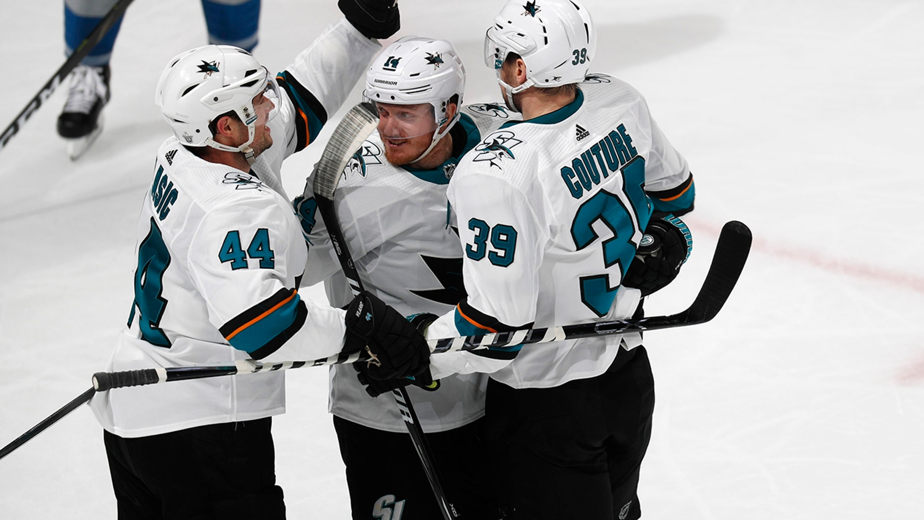 San Jose Sharks defenseman Marc-Edouard Vlasic, left, celebrates with center Gustav Nyquist and center Logan Couture, right, after his goal against the Colorado Avalanche during the third period of Game 3 of an NHL hockey second-round playoff series Tuesday, April 30, 2019, in Denver. The Sharks won 4-2. (AP Photo/David Zalubowski)