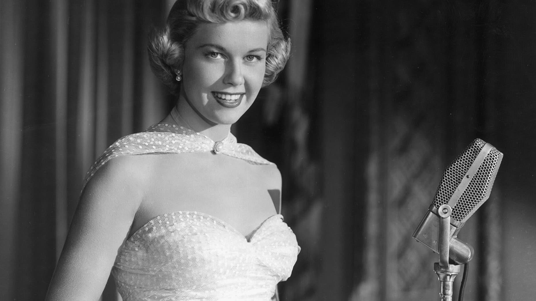 """A promotional portrait of American singer and actor Doris Day smiling as she stands behind a microphone, from director Michael Curtiz's film, """"Young Man with a Horn."""""""