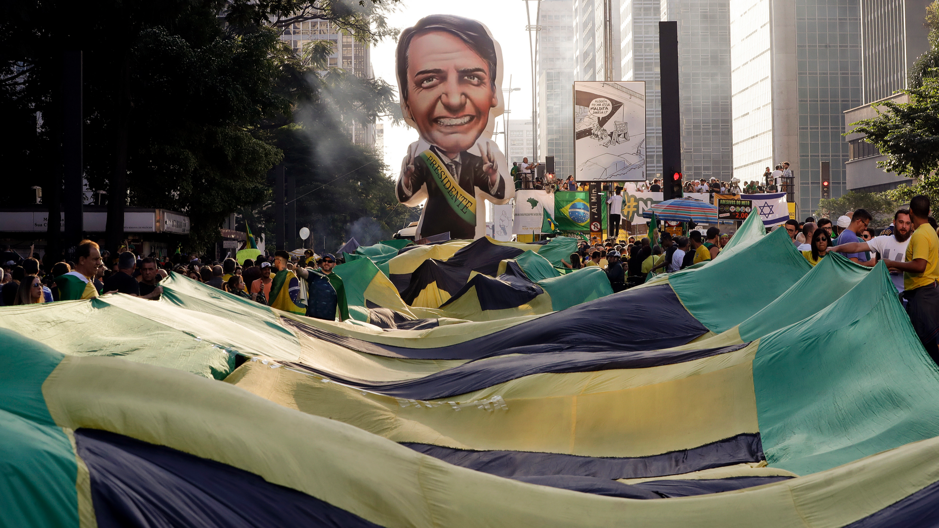 Supporters of Brazil's President Jair Bolsonaro feature a large, inflatable doll in his image as they demonstrate along Paulista Avenue in Sao Paulo, Brazil, Sunday, May 26, 2019. The pro-Bolsonaro rally follows anti-government protests against education budget cuts as the president also battles an uncooperative Congress, a family corruption scandal and falling approval ratings after five months in office. (AP Photo/Andre Penner)