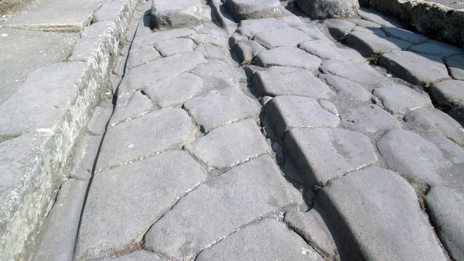 The passage of carts over decades could cause ruts (like the one shown here), particularly in high-traffic areas of Pompeii.
