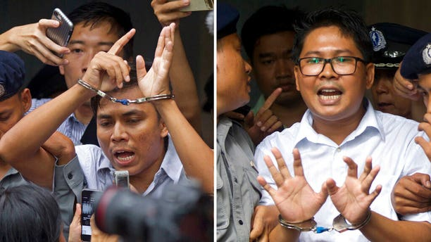 FILE: Reuters journalists Kyaw Soe Oo, left, and Wa Lone, are handcuffed as they are escorted by police out of a court in Yangon, Myanmar.