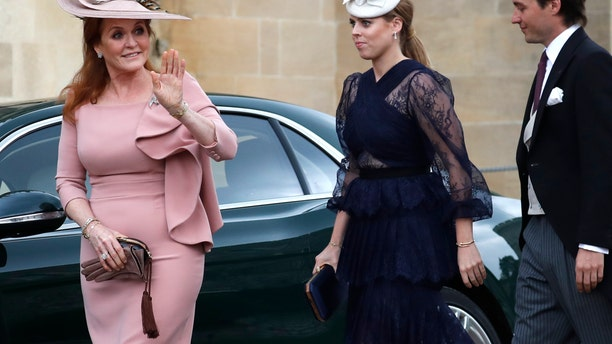 Britain's Sarah, Duchess of York, left, waves as she arrives with Princess Beatrice, center, and Edoardo Mapelli Mozzi for the wedding of Lady Gabriella Windsor and Mr Thomas Kingston at St George's Chapel, Windsor Castle in Windsor, Saturday, May 18, 2019.. (AP Photo/Frank Augstein, Pool)